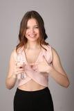 夫人把她的手指指向瓶水 关闭 灰色背景 免版税图库摄影