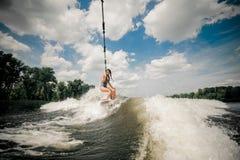 夫人拖曳与在汽艇后的wakeboard由缆绳 图库摄影