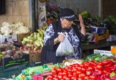 夫人摊位持有人用她的被举的手,她用新鲜蔬菜填装一个塑料袋在J的Mahane耶胡达市场上 库存图片