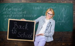 夫人教育家在教室为新的学年做准备 新的学校季节初期  妇女老师正式衣服举行 免版税库存照片