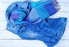夫人时尚牛仔布背心和一条蓝色围巾 库存图片