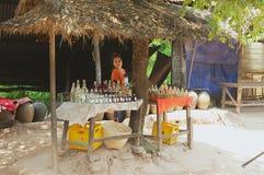 夫人有当地被生产的米酒精的出售瓶在一家街道商店在禁令Xabg干草村庄旅馆琅勃拉邦,老挝 库存照片