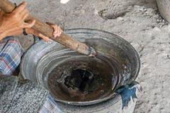 夫人煮沸了从桄榔的糖在平底锅 煮沸的水 嚼糖 室外烹调 库存照片