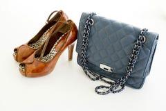 夫人用皮革包盖蓝色提包,并且高跟鞋的棕色颜色穿上鞋子i 免版税图库摄影