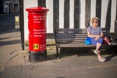 夫人由著名红色岗位箱子坐了在英国 库存照片