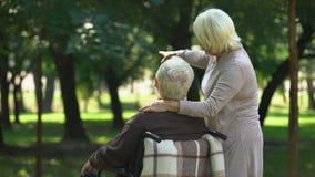 夫人谈话与残疾丈夫,走在公园,指向在距离的妇女 股票录像