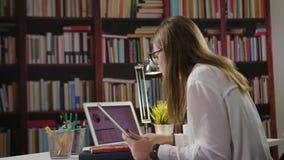 夫人Using一台膝上型计算机和一种片剂在图书馆里 免版税图库摄影