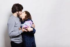 年轻夫妇一个热情的亲吻  亲吻她的男朋友的一名愉快的妇女是愉快和感激的从他接受礼物 Lo 库存照片