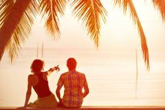 年轻夫妇一起坐在棕榈树和看下往s 免版税库存照片