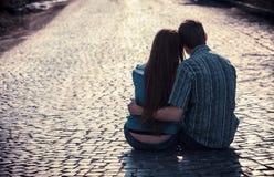 夫妇一起坐街道少年 免版税库存图片