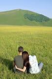夫妇一起坐象草的领域在反对山 免版税库存照片