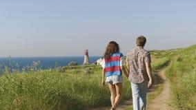 年轻夫妇一起走holging的手,谈话和笑在沙子足迹在灯塔附近在海滨峭壁 backarrow 股票视频