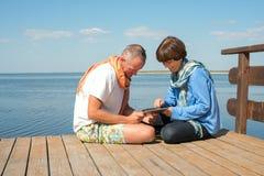夫妇与使用片剂个人计算机的朋友联络 库存照片