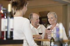 夫妇与客商的品尝酒前景的 免版税库存图片