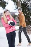 夫妇与有战斗少年的雪球 免版税库存图片