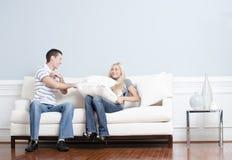 夫妇与有战斗枕头沙发年轻人 库存图片