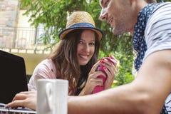 年轻夫妇与膝上型计算机一起使用户外 免版税库存照片