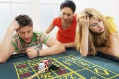 夫妇丢失打赌以朋友在轮盘赌表上 免版税库存图片