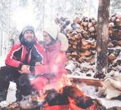 夫妇临近在冬天风景的篝火 免版税库存图片