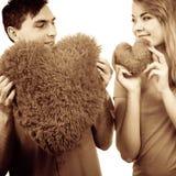 夫妇举行红色心形的枕头爱标志 免版税图库摄影