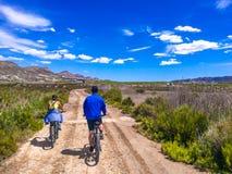 夫妇乘坐的自行车看法在一条土路的在美丽的parkland 库存图片
