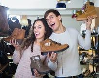 年轻夫妇买的冬天鞋子 免版税库存照片