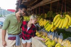 夫妇亚洲人果子买新鲜食品、年轻人和妇女游人异乎寻常的假期的街市 库存图片