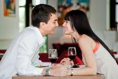 夫妇亲吻在膳食 免版税图库摄影