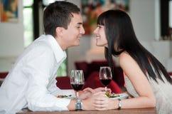 夫妇亲吻在膳食 免版税库存照片