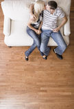 夫妇亲吻的双人沙发坐的年轻人 图库摄影