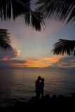 夫妇亲吻的浪漫剪影日落 免版税库存照片