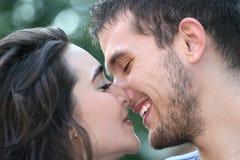 夫妇亲吻的爱户外年轻人 免版税图库摄影
