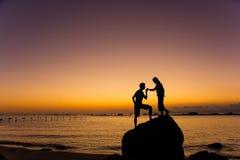 夫妇亲吻剪影在海滩的在日出和日落 库存照片