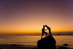 夫妇亲吻剪影在海滩的在日出和日落 免版税库存照片