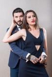 年轻夫妇优美穿戴了拥抱在灰色背景 库存图片