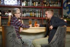夫妇传达坐在酒吧,饮用的啤酒和笑 户内 免版税库存照片
