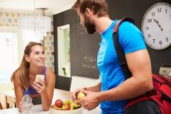 夫妇佩带的健身房衣物谈话在厨房里 免版税库存图片