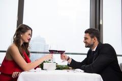 夫妇使叮当响的杯侧视图红葡萄酒,当庆祝st情人节时 库存照片