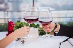 夫妇使叮当响的杯播种的射击红葡萄酒,当庆祝st情人节时 库存照片