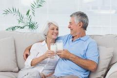 夫妇使叮当响的杯牛奶 库存照片