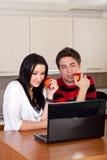夫妇使用年轻人的厨房膝上型计算机 库存图片