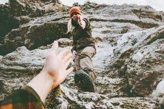 夫妇供以人员,并且给手的妇女帮助攀登山爱并且移动生活方式概念 远足冒险的年轻家庭 免版税图库摄影