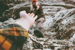 夫妇供以人员,并且给手的妇女帮助攀登落矶山脉爱并且移动生活方式 库存图片