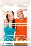 夫妇倒空冰箱 库存照片