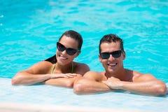 夫妇倾斜的游泳池边 免版税库存图片