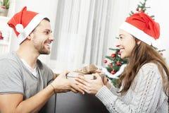 年轻夫妇做一prenent圣诞节的 免版税图库摄影
