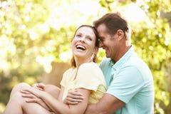 夫妇公园休息的结构树年轻人 免版税图库摄影