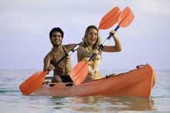 夫妇划皮船他们的年轻人 图库摄影