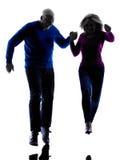 夫妇前辈跑的跳跃的愉快的剪影 免版税图库摄影