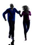 夫妇前辈跑的跳跃的愉快的剪影 库存图片